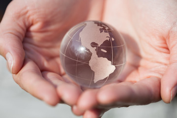 Model holding crystal glass globe in hands with care