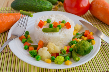 Rice with vegetables steamed on a white plate, laid out in a circle. Vegan. The top view.