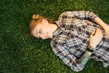 Young woman lying on grass in park and smile
