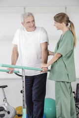 Senior man walking with therapist help in rehab studio