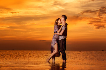 Beautiful young couple of lovers is kissing at red tropicsl sunset