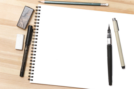 Blank white notepad with pens on wooden table