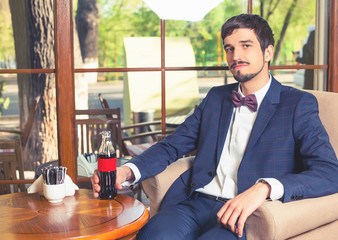 Handsome male sitting at cafe and holding fresh drink cola