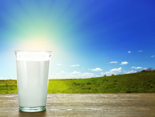 Glass of milk on wooden table against green field and blue sky background