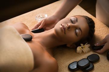 Beautiful girl has stone massage.