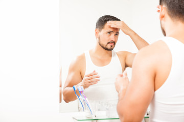 Man styling his hair in the bathroom
