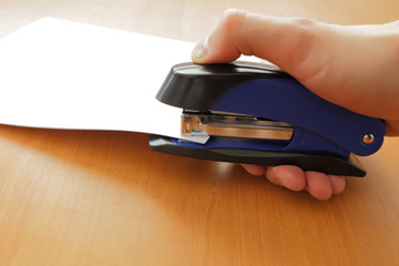 Hand holding blue stapler stapling papers, closeup view