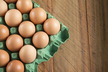 Fresh chicken eggs from the farm in a basket on a rustic wooden background