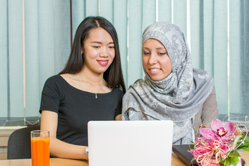 Asian and muslim girls working on a laptop