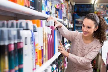 Woman choosing hairspray in supermarket.