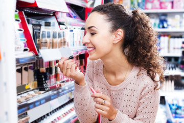 Young brunette selecting lip gloss