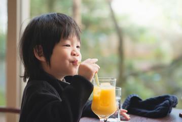 child drinking fresh orange juice