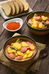 Hungarian Paprikas Krumpli (Potato with Paprika), a stew made of potato, onion, pepper, tomato and sausage (Selective Focus, Focus in the middle of the dish in the first bowl)
