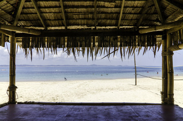 beautiful tropical beach with white sandy beach from bamboo hut. beach volley ball net on background.
