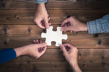 ジグソーパズルのピースを持っている人間の手