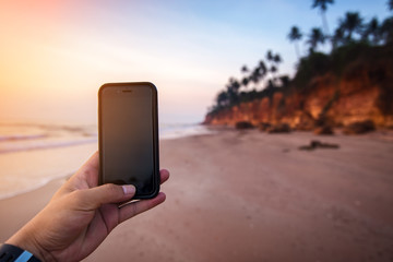 Hand holding smart phone ready to take photos of the beach at sunrise