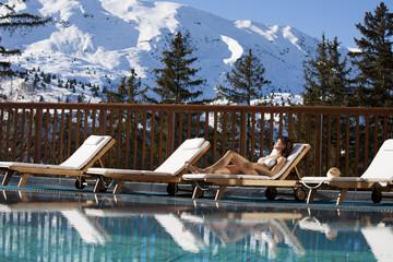 femme allongée au bord d'une piscine dans les montagne enneigées