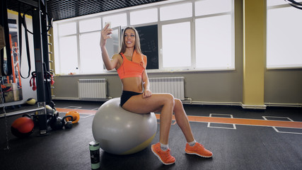fitness, lifestyle, technology and people concept - young woman with smartphone taking selfie in gym