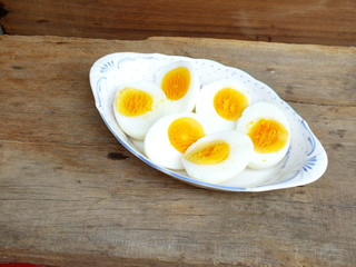 boiled eggs on plate and wooden background close up
