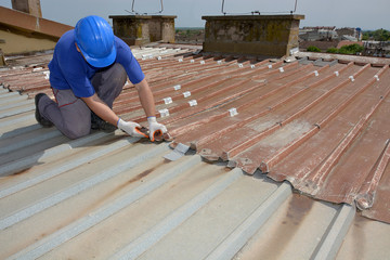 construction worker inspects old metal roof