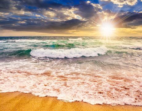 sea waves crashing on sandy beach  at sunset