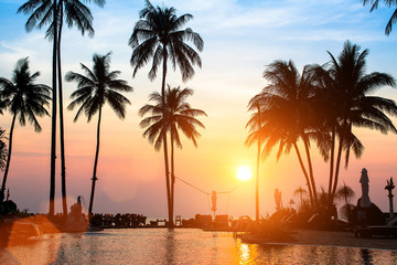 Beautiful sunset with silhouettes of palm trees on a tropical beach.