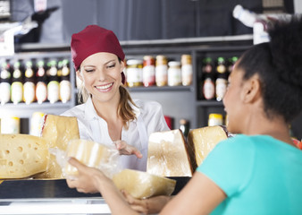 Saleswoman Assisting Young Customer In Buying Cheese