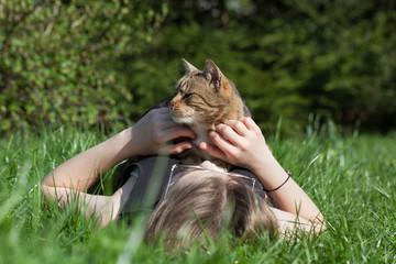 Woman petting cat  in the garden