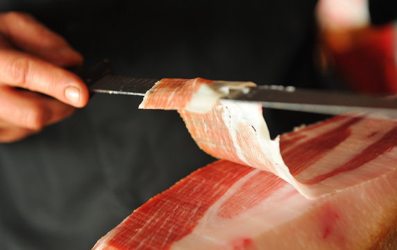 Slicing of italian dry-cured ham prosciutto. Toned image. Selective focus point