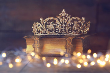 low key image of decorative crown on old book. vintage filtered