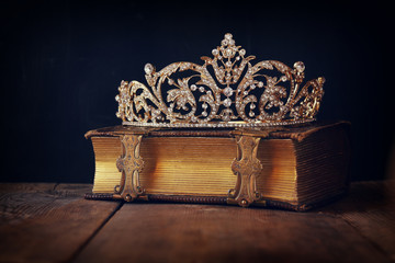 low key image of decorative crown on old book. vintage filtered.