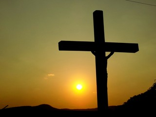 Cross with Jesus Christ and sunset