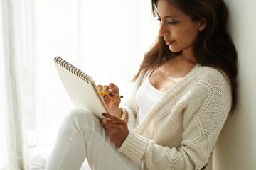 Beautiful Hispanic woman drawing sketch in album