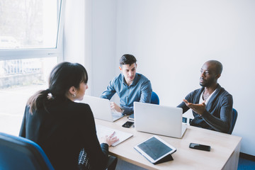 Group of contemporary multiethnic business people working together using multimedia devices like smart phone and tablet - working, business, start up concept