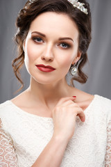 Elegant young woman with perfect makeup and hair style in a white dress. Beauty fashion portrait with accessories