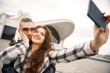 Young and happy couple having fun in the city is photographed on a smartphone