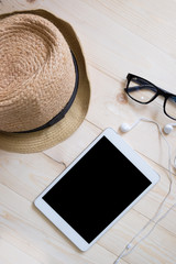 top view of hat woman glasses earphone and blank screen of tablet device over wooden table.