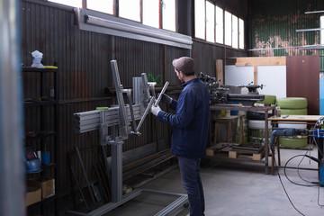 Professional worker looking at metal bar