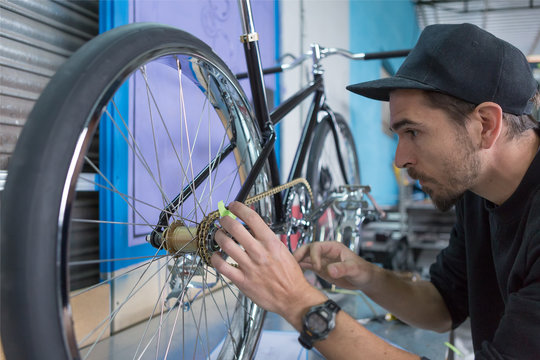 Side view of craftsman taking measurements of bike