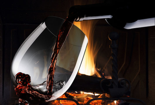 glass with red wine near the fireplace