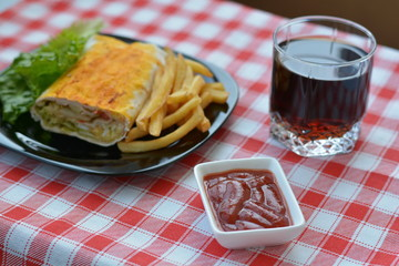 Cola, ketchup, wrap, fried potatoes on the red napkin