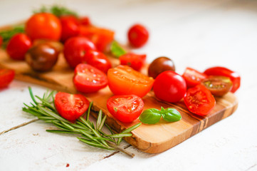 Colorful tomatoes on board on wooden background