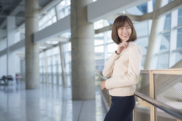 Attractive asian business woman smiling outside office