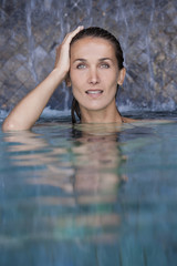 belle femme sous des chutes d'eau dans une piscine
