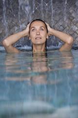 belle femme dans une piscine sous une cascade