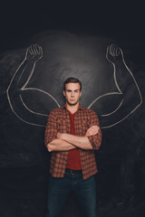 Serious young man with drawn muscular arms on the background of