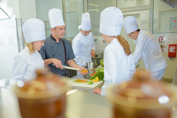 Chef teaching students on cookery course Wall mural