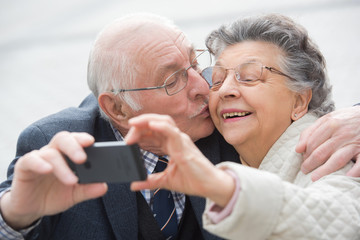 elderly couple taking a selfie