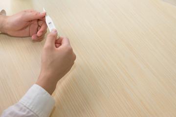 体温計を持つ女性