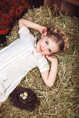 Portrait of girl in white dress on the haystack